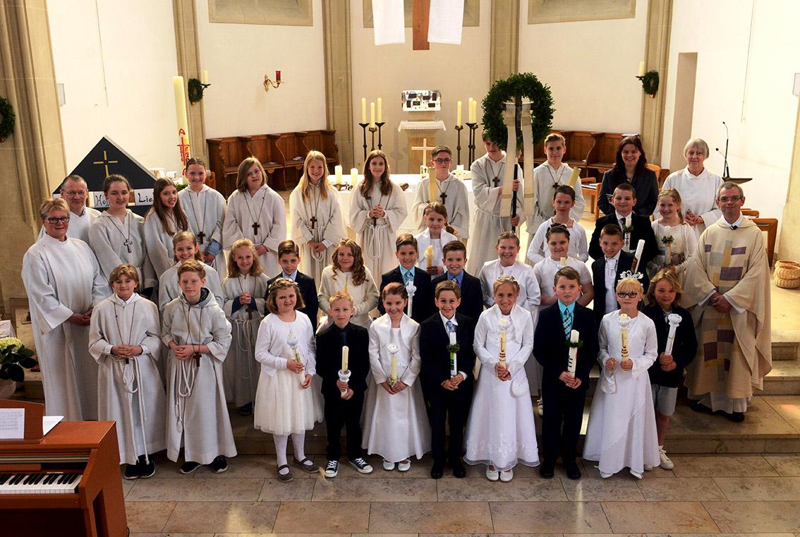 Die Gruppe der Erstkommunionkinder mit Messdiener, Lektoren und Kommunionhelfern und v.r. Pfarrer Thomas Hüwe, Gertrud Helming und Andrea Hotopp